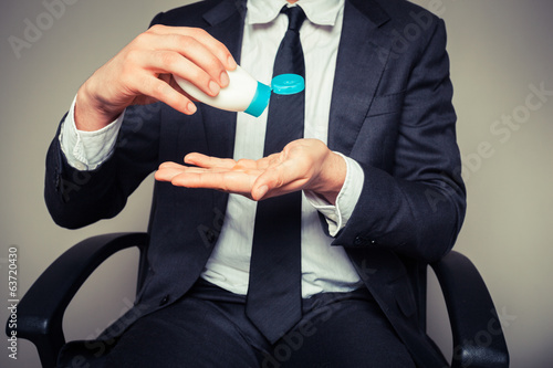 Businessman applying sun screen