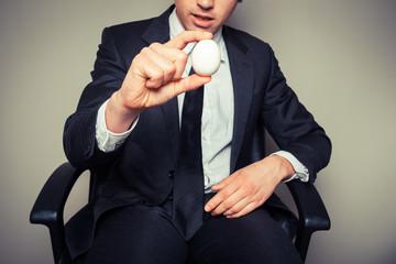 Businessman holding an egg