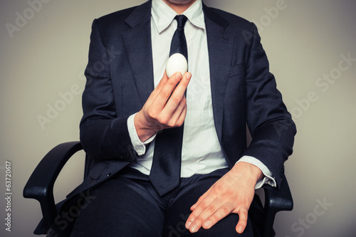Businessman holding an egg