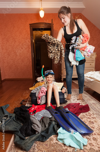 girl sitting in suitcase while woman throwing clothes in it
