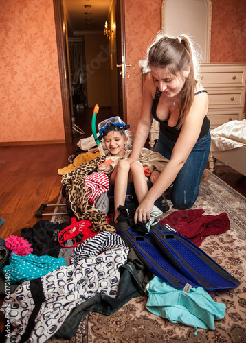 mother packing clothes and daughter in tourist suitcase
