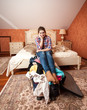 depressed woman sitting on unpacked suitcase