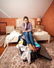 depressed woman sitting on unpacked suitcase