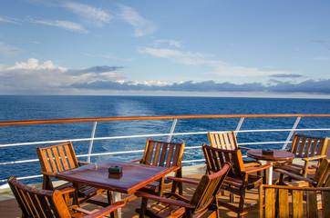 Chairs and tables on the outdoor deck of a cruise ship.