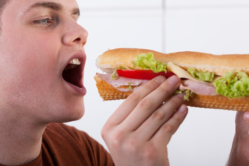 Teenager biting sandwich