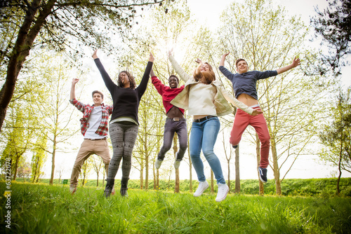 Group of Happy College Students Jumping at Park,Italy