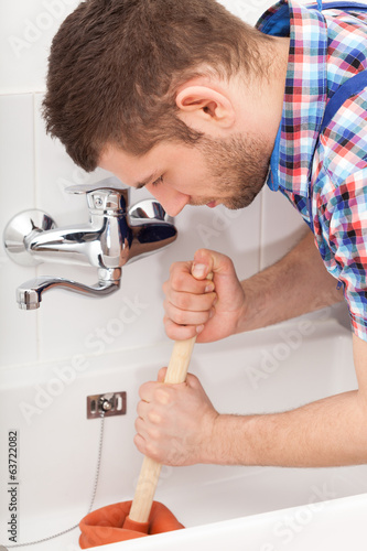 Plumber unclogging a bathtube drain