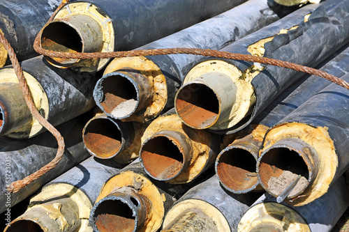 Rusty steel pipe with heat insulation on construction site