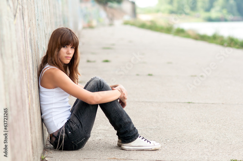 Sad teenage girl sitting alone
