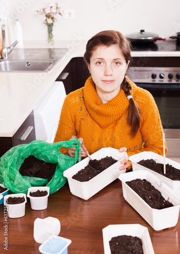 Girl making ground  in pots for seedlings