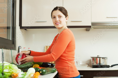 woman washing  vegetables in sink at  kitchen