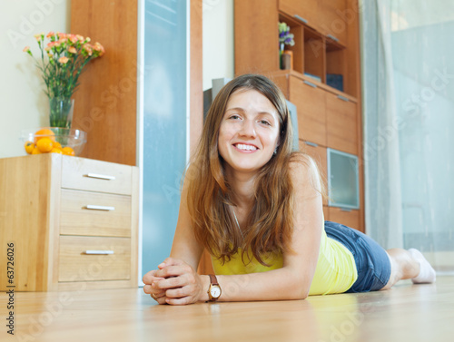 Happy beautiful woman on parquet floor