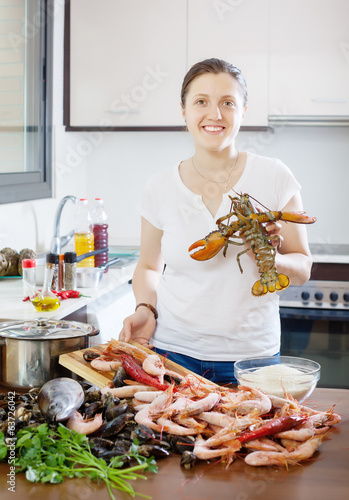 Happy woman with lobster   in home kitchen