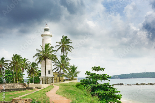 Lighthouse and palm trees on background sky
