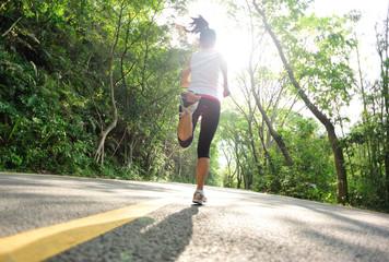 Runner athlete running on road.