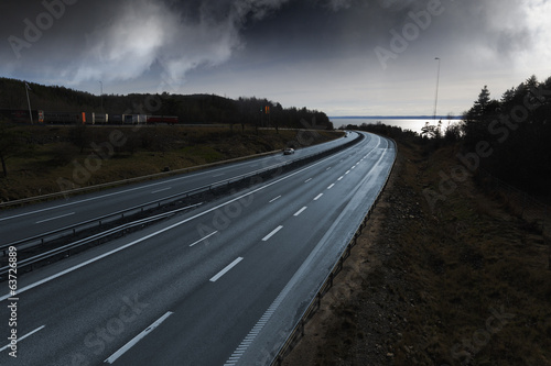 large freeway, evening light and storm clouds above