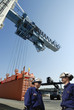 port workers directing loading of cargo-containers
