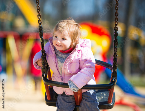 little  girl riding on a swing