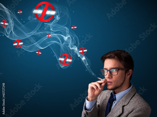Attractive man smoking dangerous cigarette with no smoking signs