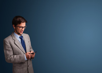 Young man standing and typing on her phone with copy space