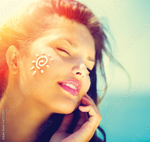 canvas print picture Beauty Girl Applying Sun Tan Cream on her Face. Sun Tanning