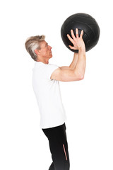 Senior fitness man exercising with black wall ball. Isolated on