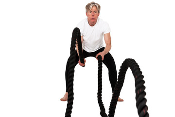 Senior fitness man exercising with black battling rope. Isolated
