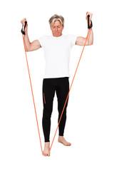 Senior fitness man exercising with orange elastics. Isolated on
