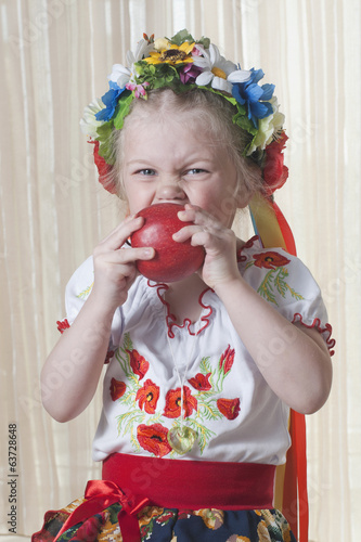 The girl of 4 years in a national Ukrainian suit eats red apple
