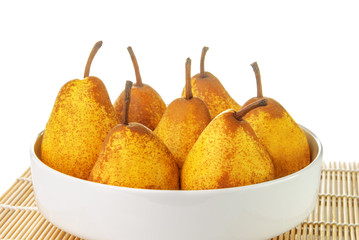 Yellow ripe pears in a white bowl