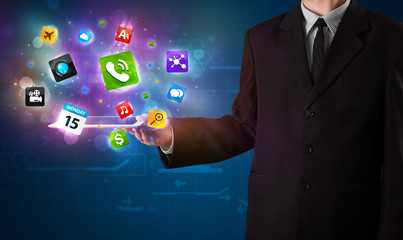 Businessman holding a tablet with modern colorful apps and icons
