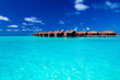 Overwater villas in blue tropical lagoon