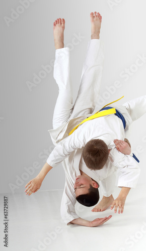 Boy with a blue belt throws boy with yellow belt