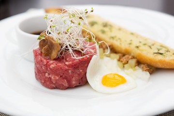 Close up of tartare beef with fried egg and garlic bread