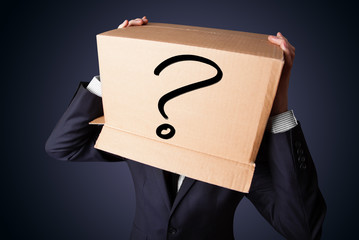 Businessman gesturing with a cardboard box on his head with ques