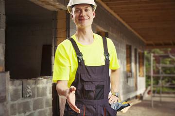 Builder offering handshake at construction site