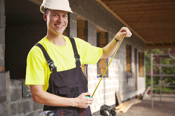Contractor taking measures smiling at construction site