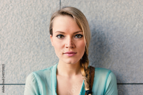 Intimate blonde woman portrait against wall.