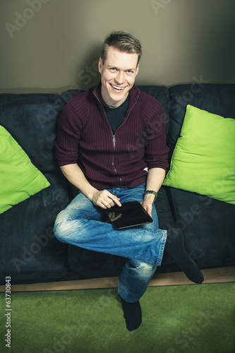 Man sitting on sofa using digital tablet looking up