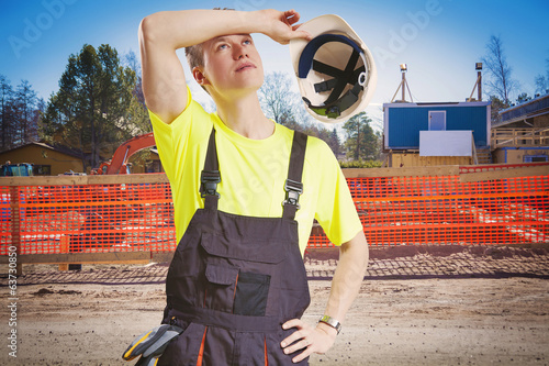 Exhausted worker takes helmet of for a break