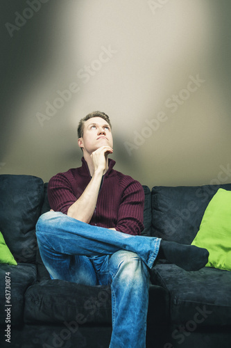 Man sitting on sofa thinking and looking up