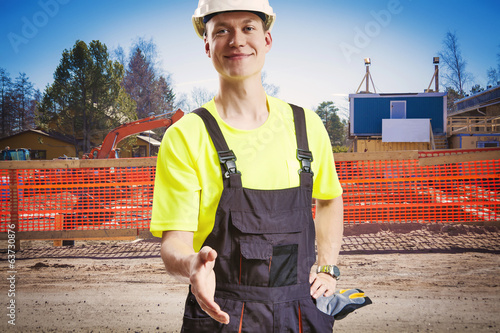 Builder offering handshake at construction site