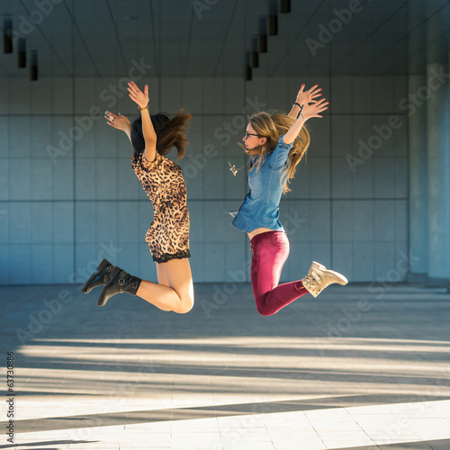 Young women portrait jumping with modern building as background.