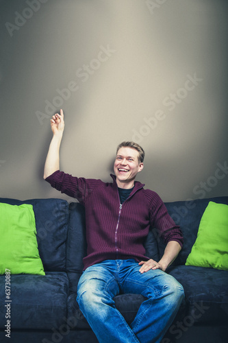 Man sitting on sofa laughing pointing up to wall