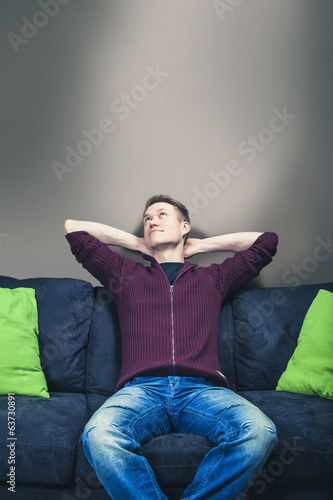 Man sitting on sofa relaxing and dreaming