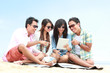 Group Friends Enjoying Beach Holiday together with tablet pc