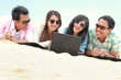 Group Friends Enjoying Beach Holiday together with laptop