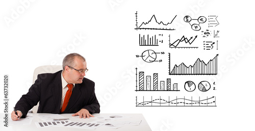 businessman sitting at desk with statistics and graphs