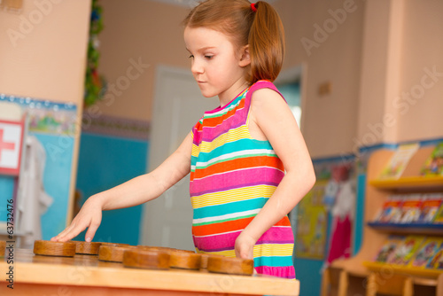 Cute girl playing checkers at daycare