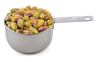 Shelled pistachio nuts in a metal cup measure